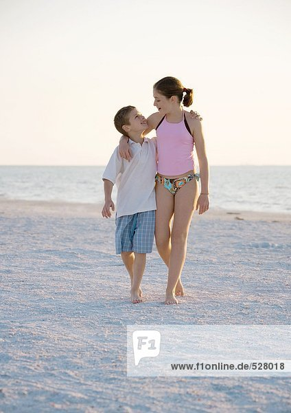 Girl and boy walking with arms around each other's shoulder's on beach