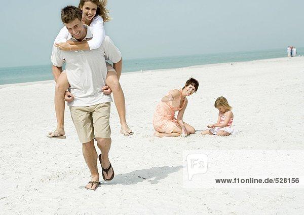 Vater trägt Teenager-Tochter Huckepack am Strand  während Mutter zuschaut.