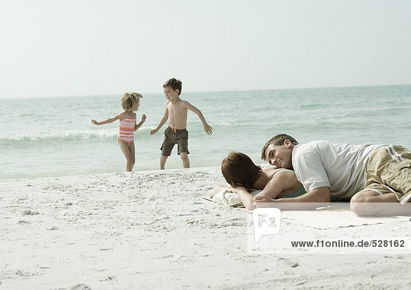 Parents lying on beach while children play in background