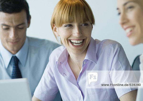 Geschäftskollegen  die zusammen arbeiten  lächelnd