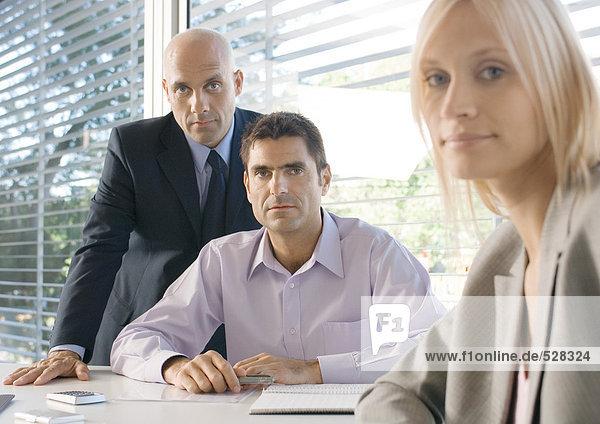Drei Geschäftsleute im Büro  mit Blick auf die Kamera