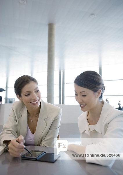Zwei Geschäftsfrauen mit elektronischem Organizer