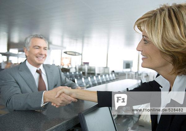 Flugbegleiterin beim Händeschütteln mit dem Passagier