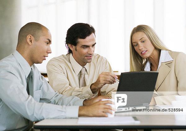 Drei junge Führungskräfte arbeiten gemeinsam am Laptop