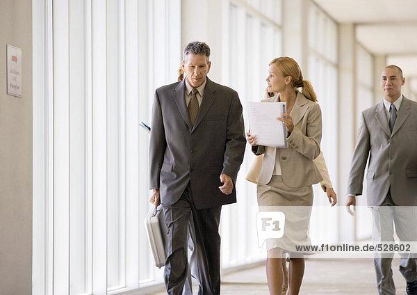 Gruppe von Führungskräften auf dem Weg durch den Korridor