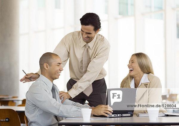 Gruppe junger Führungskräfte lacht  ein Mann steht und klopft den zweiten Mann auf den Rücken.