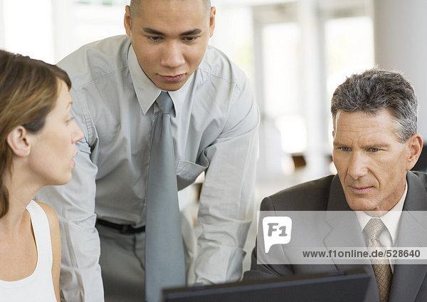 Drei junge Führungskräfte arbeiten zusammen rund um den Laptop