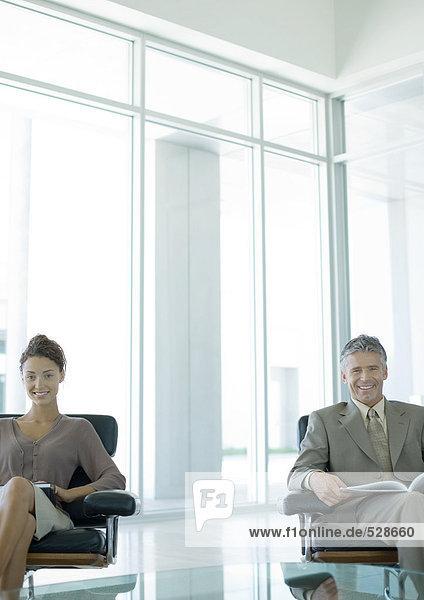 Zwei Geschäftsleute sitzen in der Büro-Lobby und lächeln vor der Kamera. Zwei Geschäftsleute sitzen in der Büro-Lobby und lächeln vor der Kamera.
