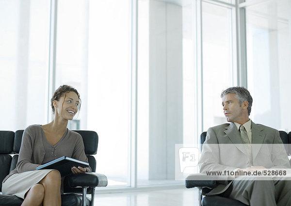 Zwei Geschäftsleute chatten in der Büro-Lobby Zwei Geschäftsleute chatten in der Büro-Lobby