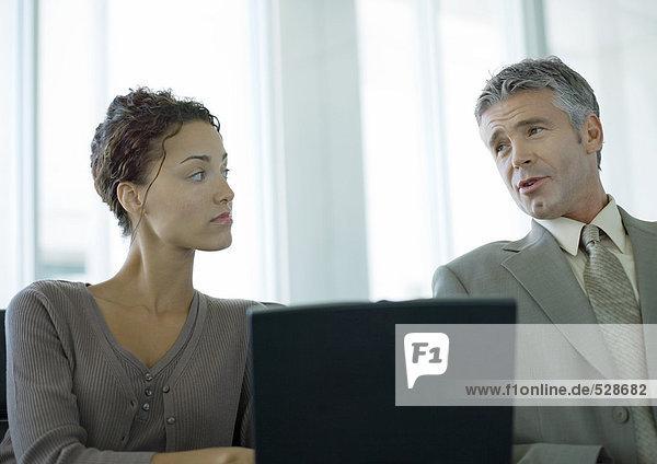 Zwei Geschäftskollegen bei der Diskussion und Nutzung des Laptops Zwei Geschäftskollegen bei der Diskussion und Nutzung des Laptops