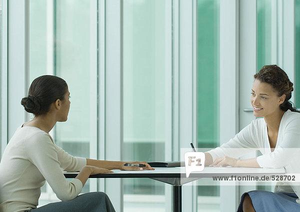 Zwei Frauen  die sich am Tisch gegenüber sitzen und arbeiten. Zwei Frauen, die sich am Tisch gegenüber sitzen und arbeiten.