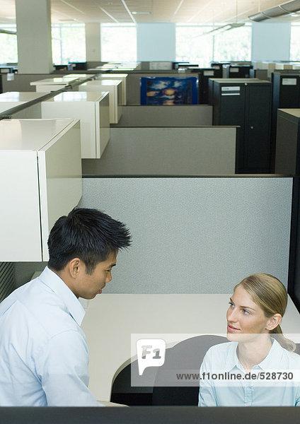 Zwei Büroangestellte sprechen in der Kabine