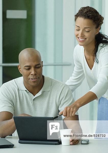 Frau lehnt sich über die Schulter des Mannes und zeigt auf den Laptop-Bildschirm. Frau lehnt sich über die Schulter des Mannes und zeigt auf den Laptop-Bildschirm.