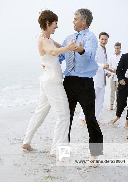 Leute in formaler Kleidung tanzen am Strand