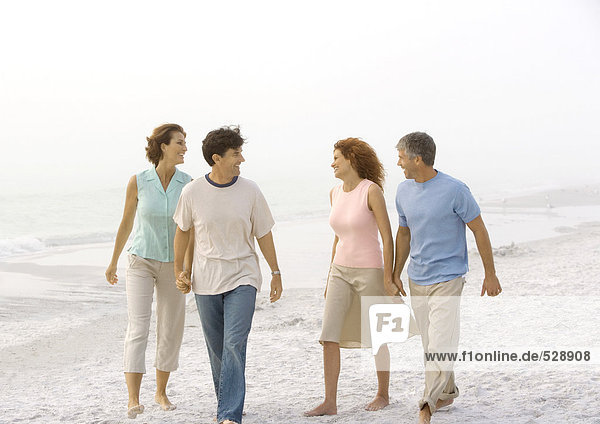 Zwei reife Paare  die am Strand spazieren gehen und Händchen halten.