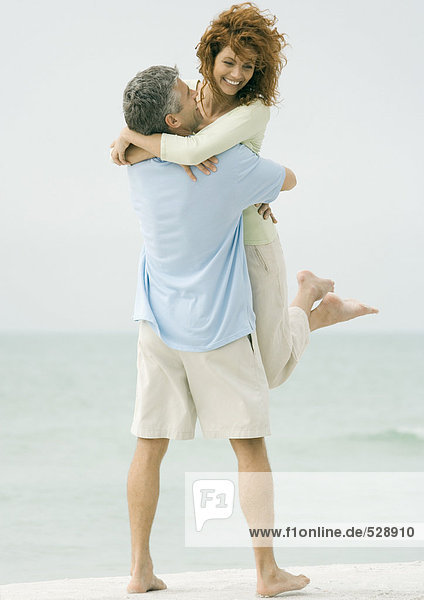 Mature couple  man picking up woman on beach