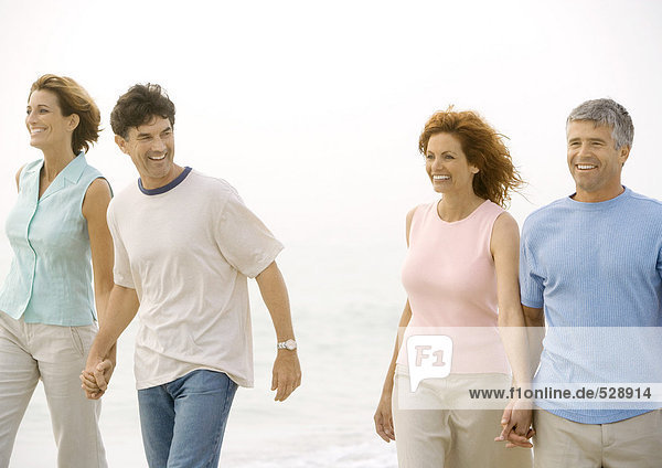 Zwei erwachsene Paare  die am Strand spazieren gehen.