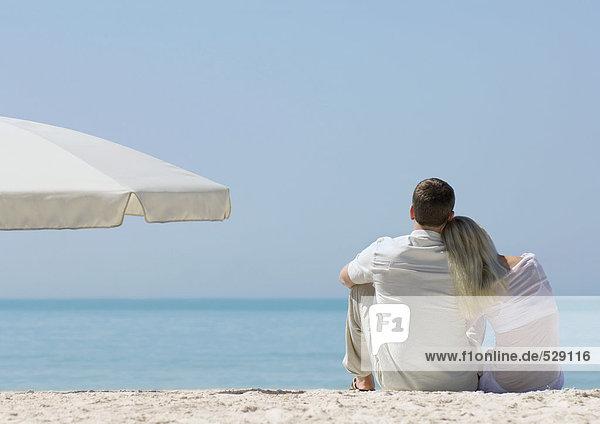 Paar am Strand sitzend  Frau ruht Kopf auf der Schulter des Mannes  Rückansicht