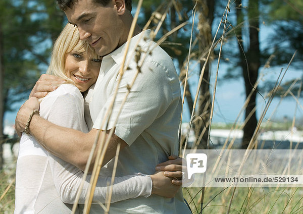Paar in hohem Gras umarmend