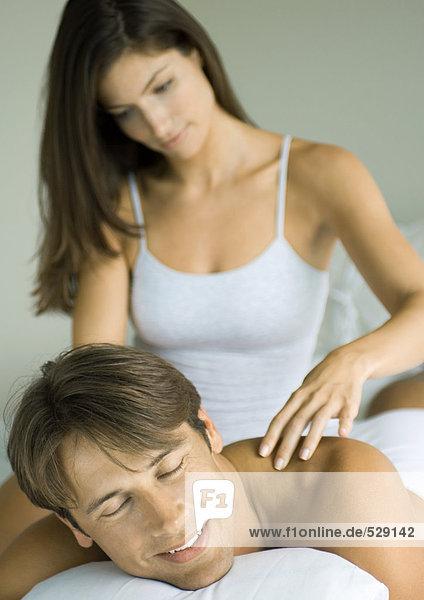 Mann im Liegen, Frau massiert seine Schultern