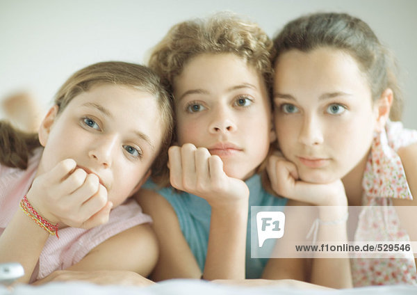 Preteen girls leaning on elbows  looking out of frame