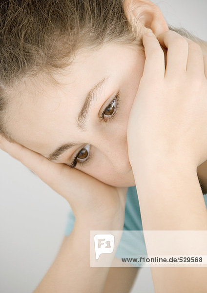 Preteen girl holding head  looking down