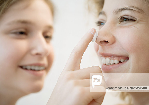 Girl putting lotion on friend's nose