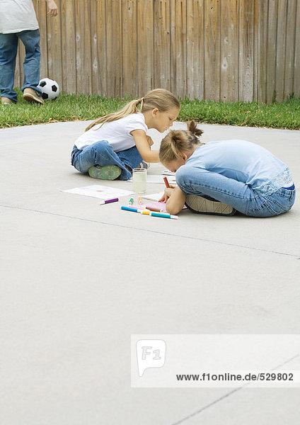 Kinder sitzen auf der Einfahrt  zeichnen