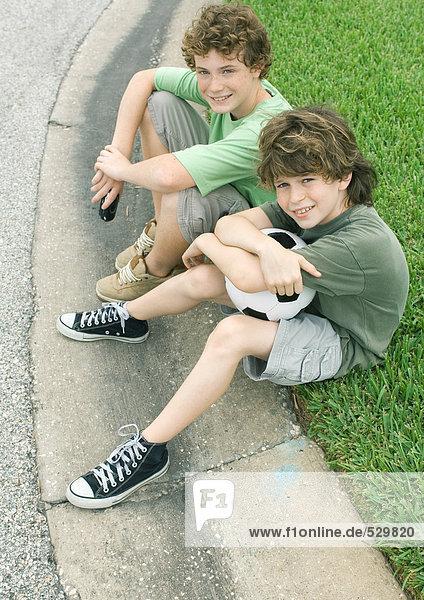 Vorstadtkinder auf dem Bordstein sitzend