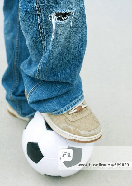 Junge ruht Fuß auf Fußball  Nahaufnahme