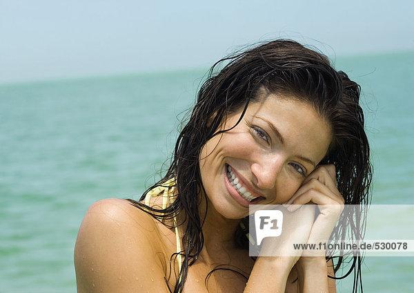 Frau mit nassem Haar lächelnd  Meer im Hintergrund