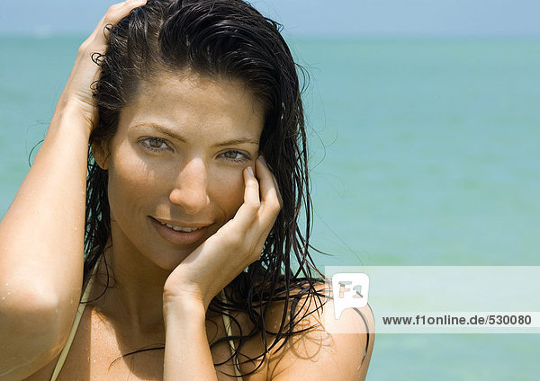 Frau hält Kopf  lächelt in die Kamera  Meer im Hintergrund