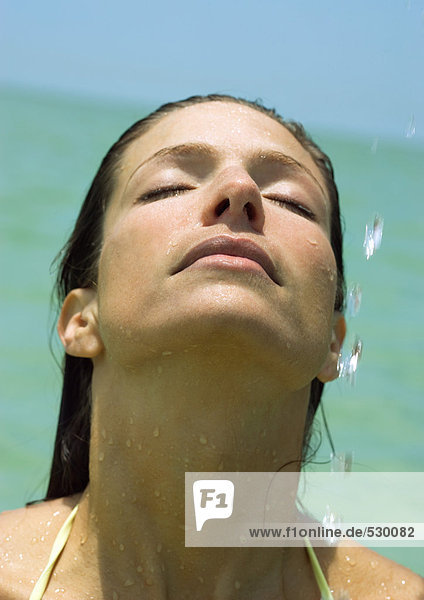 Frau mit Kopf zurück und Wassertropfen in der Luft  Meer im Hintergrund