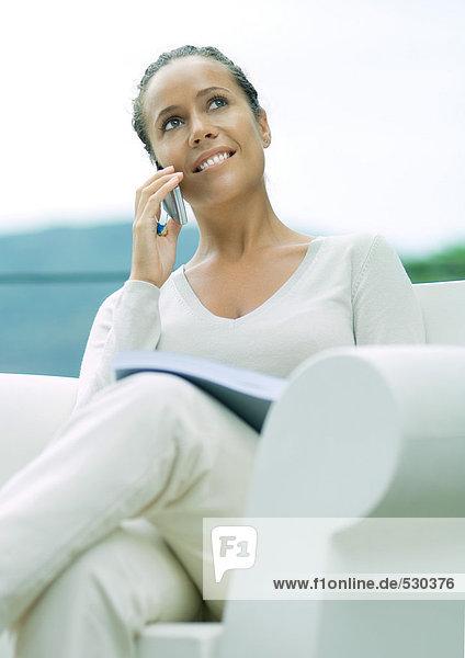 Frau im Sessel sitzend  mit Handy