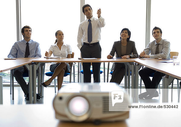 Businesspeople watching presentation  videoprojector in foreground