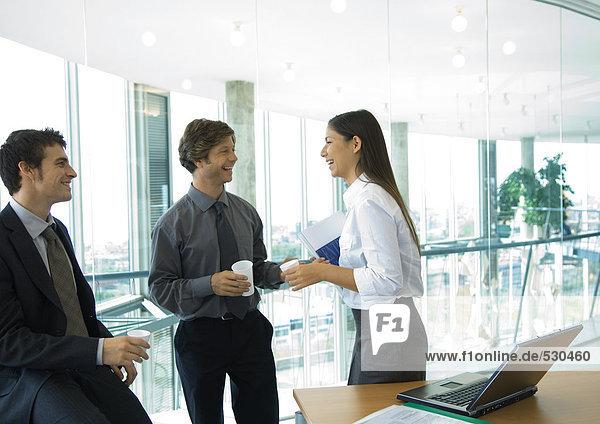 Drei Büroangestellte  die mit Tassen Kaffee stehen und sich unterhalten