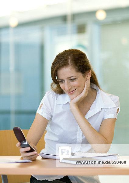 Frau am Schreibtisch sitzend  lächelnd und auf das Handy schauend