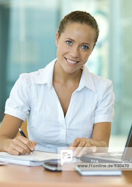 Businesswoman sitting at desk  writing  smiling at camera