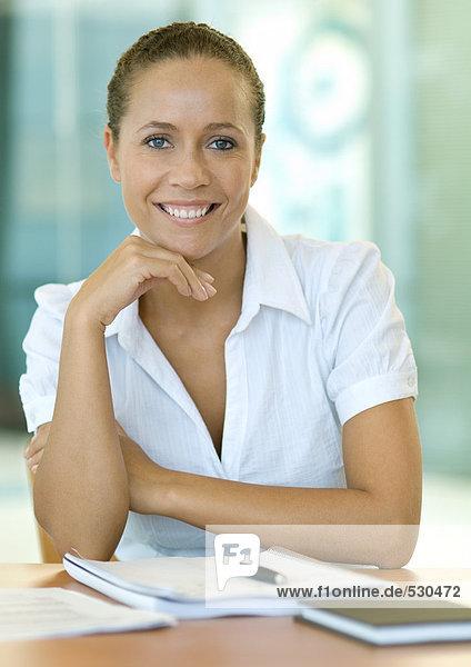 Businesswoman sitting at desk  smiling at camera  portrait