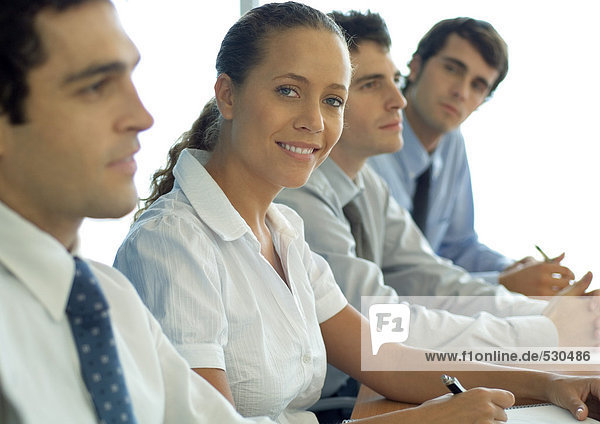 Business associates sitting at table  woman smiling at camera
