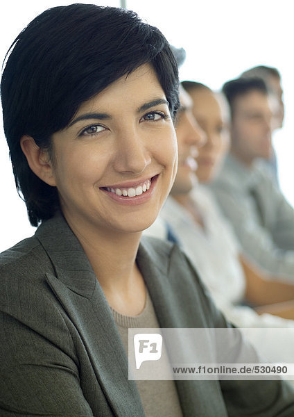 Businesswoman smiling at camera  colleagues in background