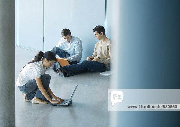 Junge Frau und zwei junge Männer mit Laptops auf dem Boden