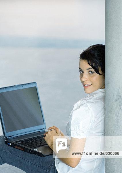 Junge Frau auf dem Boden sitzend  mit Laptop  über die Schulter schauend auf die Kamera