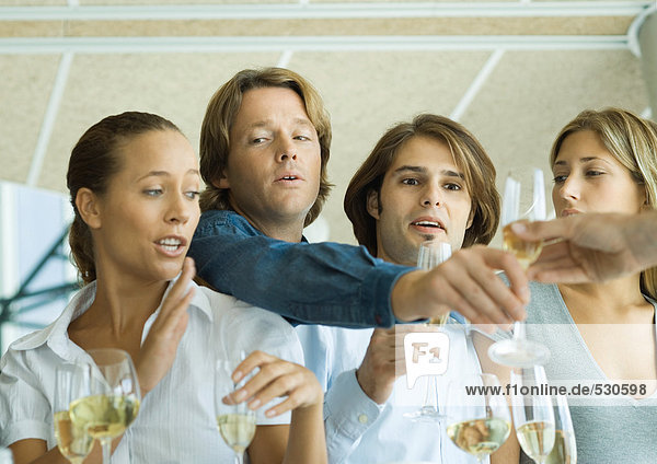 Man reaching over friends' shoulders for glass of champagne