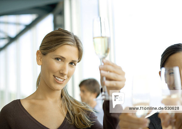 Woman holding up glass of champagne  smiling at camera
