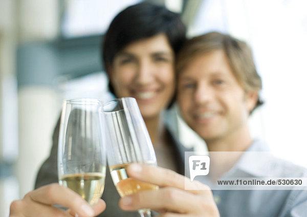 Mann und Frau klirren Champagnergläser  Fokus auf Gläser im Vordergrund
