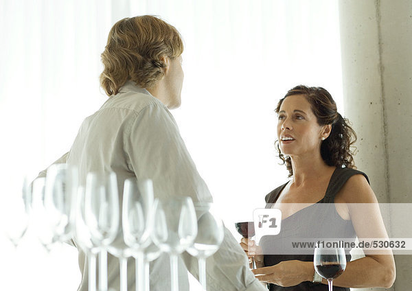 Man and woman talking during cocktail party