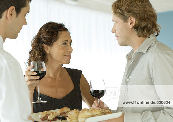 Woman smiling at man in cocktail party
