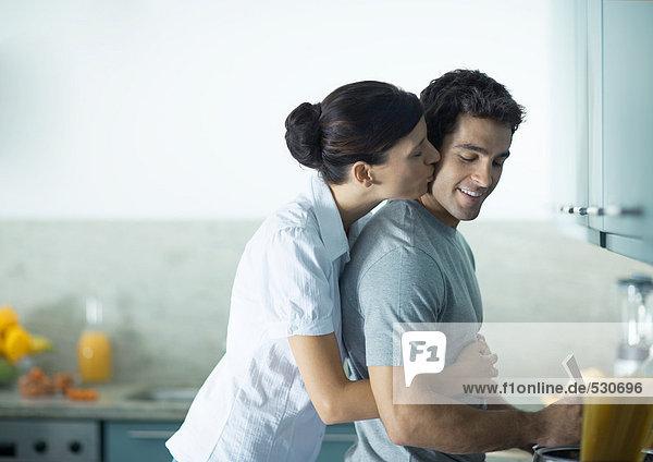 Frau küsst Mann von hinten in der Küche