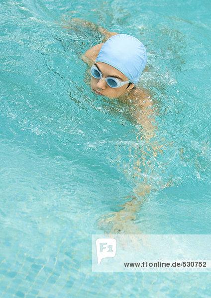 Person im Schwimmbad mit Badekappe und Schutzbrille